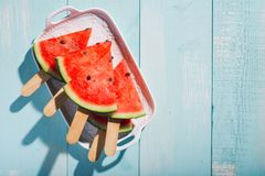 Slices of watermelon on blue wooden desk. Stock Photo