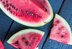 Slices of watermelon  on a dark wooden background, top view. Juicy, sweet slices of watermelon  on a dark wooden background, top view Royalty Free Stock Photos