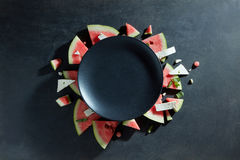 Slices of watermelon placed in a circle on black plate Stock Photo