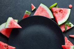 Slices of watermelon placed in a circle on black plate Royalty Free Stock Photos