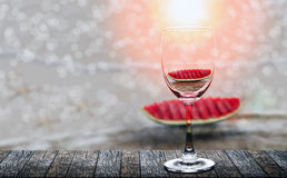 Slices of the watermelon teflected in wine glass. Slices of the watermelon reflected in wine glass on wooden table under the sunlight royalty free stock photos