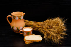 Slices of white bread, a cup of milk and a jug, a sheaf of wheat ears on a black table Stock Image
