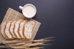 Slices of white bread with sesame seeds and milk in white glass. Slices of fresh white bread with sesame seeds and milk in white glass on black stone table Royalty Free Stock Photos