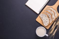 Slices of white bread with sesame seeds and milk in white glass. Slices of fresh white bread with sesame seeds and milk in white glass on black stone table Royalty Free Stock Photo