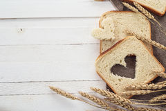 Slices of white bread and wheat ears on sacking on white boards. Royalty Free Stock Photos