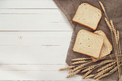 Slices of white bread and wheat ears on sacking on white boards. Royalty Free Stock Photo