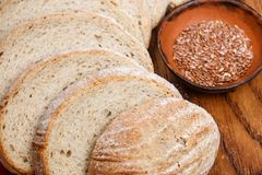 Slices of whole grain flax bread on chopping Board Stock Image