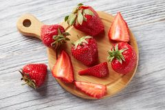 Slices and whole ripe strawberries on a wooden board on a gray wooden background. Healthy vtamin berry. Flat lay royalty free stock image