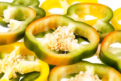 Slices of yellow and green pepper vegetables on white background.  Royalty Free Stock Images