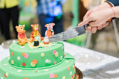 Slicing the Birthday cake with candles and Winnie the Pooh. By Disney Royalty Free Stock Photos