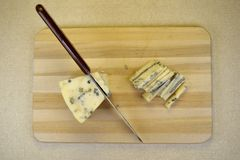 Slicing the blue cheese, top view Royalty Free Stock Photo