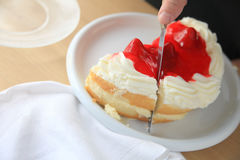 Slicing a cake with whipped cream and fruit glaze Stock Photo