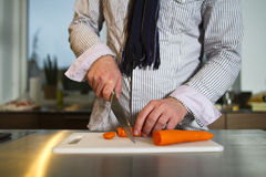 Slicing carrots. Man slicing carrots with knife Stock Images