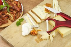 Slicing cheese, preparing for the home garden party. Fast food to wine and beer. Delicious canapes for guests. Stock Image
