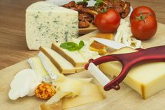 Slicing cheese, preparing for the home garden party. Fast food to wine and beer. Delicious canapes for guests. Royalty Free Stock Image