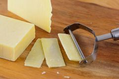 Slicing cheese. With a wire cheese slicer Royalty Free Stock Images