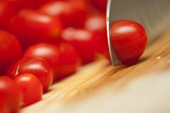 Slicing cherry tomatoes. On a wooden cutting board stock photography