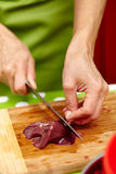 Slicing chicken liver Royalty Free Stock Image