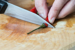 Slicing chilli pepper and knife on wooden bamboo chopping board Stock Images