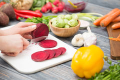 Slicing, chopping and peeling the vegetables cook. Cooking chef chop cut food prepare vegetables women salad cutting chopping mediterranean home kitchen people Royalty Free Stock Images
