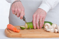 Slicing courgettes. A courgette being sliced on a wooden chopping board Royalty Free Stock Photography