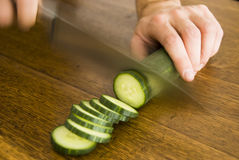 Slicing Cucumber. A hand holding a cucumber while another hand is slicing it, motion blurred Stock Images