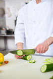 Slicing cucumber. Chef slicing fresh cucumber for salad Royalty Free Stock Photo