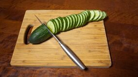 Slicing cucumber. Closeup of chopped vegetables on wooden cutting board. Stop motion animation stock video footage