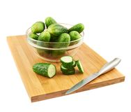 Slicing cucumber over a cutting board Royalty Free Stock Images