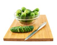 Slicing cucumber over a cutting board Stock Images