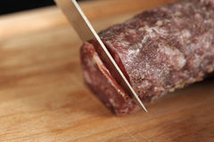 Slicing a dried sausage Royalty Free Stock Image