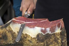 Slicing dry-cured ham prosciutto. On the street market Stock Photos