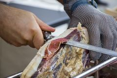 Slicing dry-cured ham prosciutto. On the street market Royalty Free Stock Image