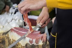 Slicing dry-cured ham prosciutto. On the street market Royalty Free Stock Photography