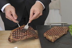 Slicing an entrecote on a carving table Stock Photos
