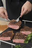 Slicing an entrecote on a carving table Stock Photo