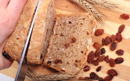 Slicing fresh bread, ears of wheat and raisins Stock Photos