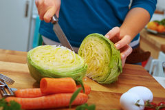 Slicing fresh iceberg lettuce Royalty Free Stock Photo