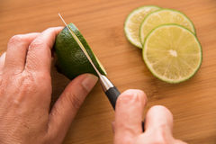 Slicing a fresh lime Stock Photo