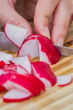 Slicing fresh radishes. Close up of a sharp knife slicing fresh organic radishes on a wooden cutting board Royalty Free Stock Images