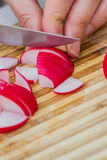 Slicing fresh radishes. Close up of a sharp knife slicing fresh organic radishes on a wooden cutting board Stock Photos