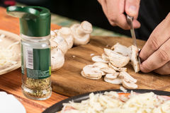 Slicing fresh raw mushrooms for baking pizza.  Stock Images