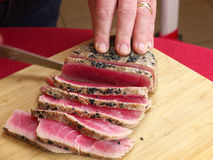 Slicing Fresh Seard tuna fish. Slicing fresh seared Tuna Fish on a wooden cutting board Stock Image