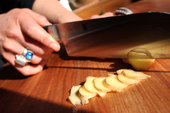 Slicing ginger. Slicing fresh ginger on a wooden chop block with a large knife Royalty Free Stock Image