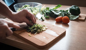Slicing greens for salad. With a knife on a wooden Board male hands Royalty Free Stock Image