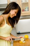 Slicing Lemons. A beautiful young Asian woman slicing lemons in the kitchen Royalty Free Stock Photo