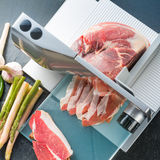 Slicing machine. Prosciutto ham and slicing machine Royalty Free Stock Photography
