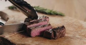 Slicing medium fillet mignon steak on wood board. Wide photo stock image
