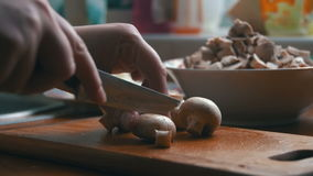 Slicing mushrooms on a kitchen board stock footage