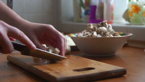 Slicing mushrooms on a kitchen board stock video